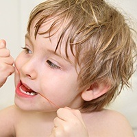 Young child flossing teeth