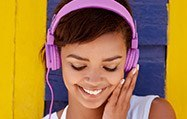 Young lady enjoying music on pink headphones