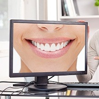 Person pointing at monitor showing person smiling