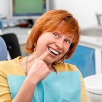 Senior woman in dental chair pointing to smile