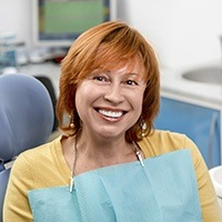 Senior lady sitting on dental chair smiling widely
