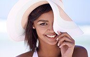 Lady wearing sunhat smiling mischievously