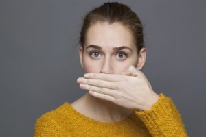 woman covering her mouth embarrassed