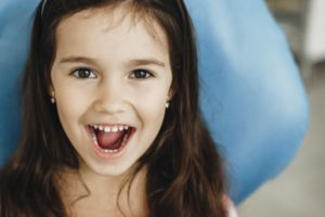 a little girl showing off her teeth