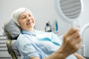 older woman admiring her dental implants in Huntington Beach in the mirror