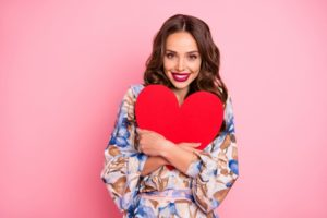 Smiling woman without gum disease holding heart cutout